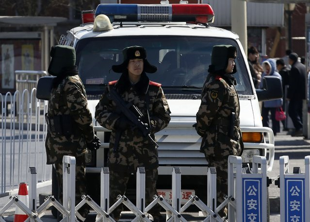 Paramilitary policemen stand guard in front of a police car ahead of the opening session of Chinese People's Political Consultative Conference (CPPCC) at Tiananmen Square in Beijing, March 3, 2015.  REUTERS/Kim Kyung-Hoon