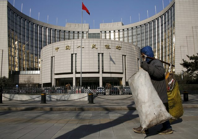 A garbage collector walks past the headquarters of the People's Bank of China, the country's central bank, in Beijing, China, January 19, 2016. (Photo by Kim Kyung-Hoon/Reuters)