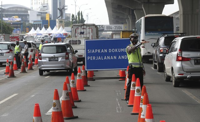 Indonesian police guard at a checkpoint during the imposition of large-scale restriction to curb the spread of the coronavirus on a toll road in Cikarang, West Java, Indonesia, Thursday, May 6, 2021. Indonesia is prohibiting travel during the popular homecoming period to celebrate Eid al-Fitr. The ban started Thursday and will last for 12 days, exempting only civil servants, police and military officers, and those who need to travel for work. (Photo by Achmad Ibrahim/AP Photo)