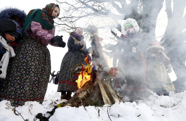 Girls warm themselves at a fire as they take part in Kolyada holiday celebrations in the village of Martsiyanauka, Belarus, January 21, 2016. (Photo by Vasily Fedosenko/Reuters)