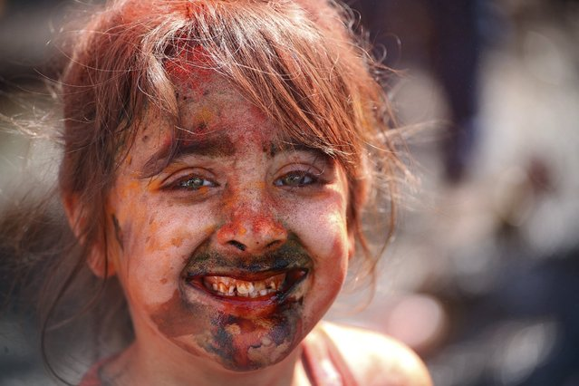 A child covered in coloured powder smiles during a spring festival celebration in Baghdad March 20, 2015. (Photo by Ahmad Mousa/Reuters)