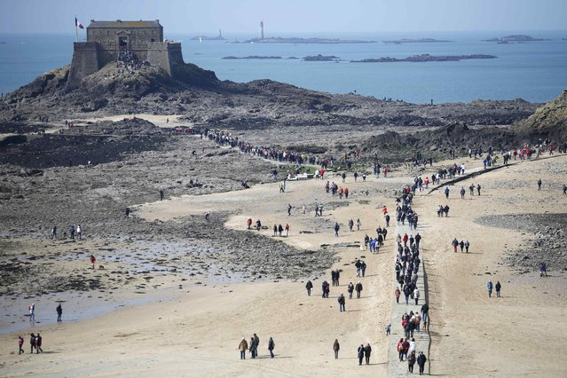 A general view of people who dot the beach during a record low tide in Saint Malo, western France, March 21, 2015. (Photo by Stephane Mahe/Reuters)