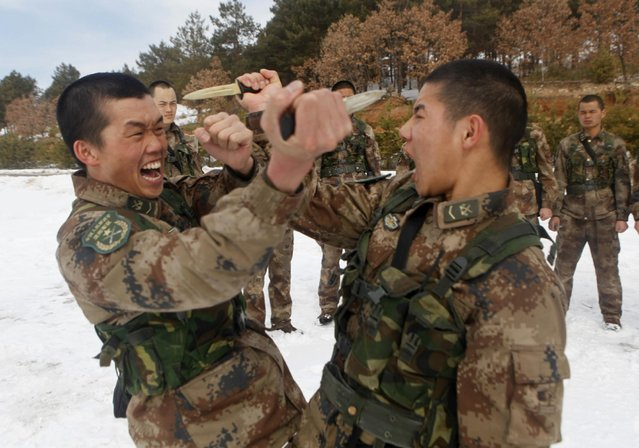 Soldiers from China's People's Liberation Army thrust daggers at each other during a training session in the city of Heihe in northeastern China's Heilongjiang province Wednesday, March 18, 2015. The Chinese government announced during this month's National People's Congress that it would increase defense spending by 10.1 percent, citing a need to modernize equipment and improve conditions. (Photo by AP Photo)