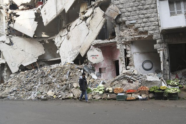 A man walks beside fresh produce for sale in front of a damaged building in Aleppo December 31, 2014. (Photo by Hamid Khatib/Reuters)