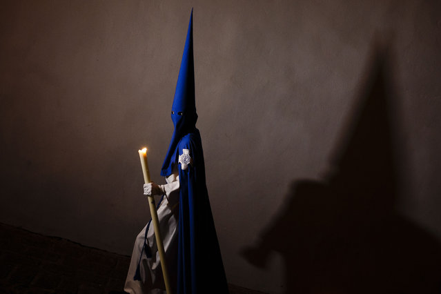 "A penitent casts his shadow as he takes part in ""Nuestro Senor Atado a la Columna, Maria Santisima de la Paz y San Juan Evangelista"" Holy Week procession in Arcos de la Frontera, Spain, Tuesday, March 31, 2015. (Photo by Daniel Ochoa de Olza/AP Photo)"