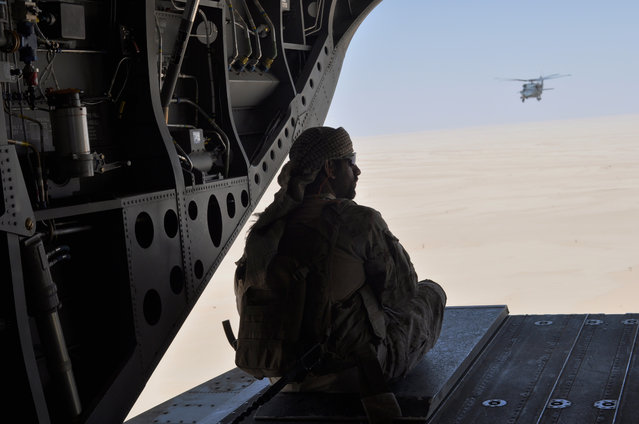 In this Monday, September 14, 2015 file photo, an Emirati soldier stands guard out the rear gate of a Chinook military helicopter, escorted by a Blackhawk helicopter, traveling from Saudi Arabia to Yemen. Saudi Arabia's offer to put boots on the ground to fight Islamic State in Syria is as much about the kingdom's growing determination to flex its military might as it is about answering U.S. calls for more help from Mideast allies. (Photo by Adam Schreck/AP Photo)