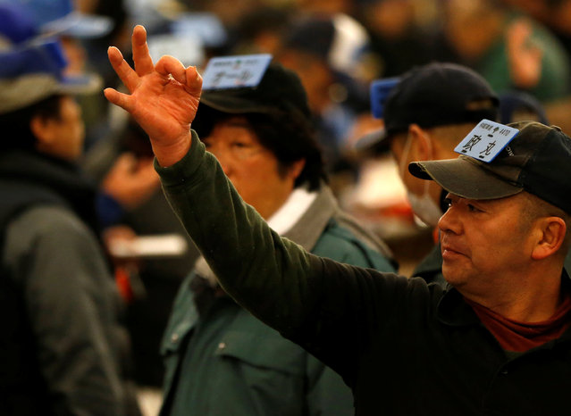 A wholesaler shows a hand sign to an auctioneer during the New Year's auction of the frozen tuna at the Tsukiji fish market in Tokyo, Japan, January 5, 2017. (Photo by Issei Kato/Reuters)
