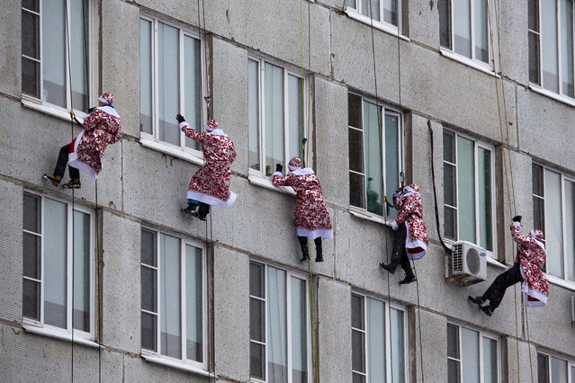 Russian emergency rescue workers dressed as Ded Moroz (Santa Claus, or Father Frost ) scale the wall of a children hospital in Moscow, Russia, Thursday, December 27, 2018. The action marked the approach of the New Year. (Photo by Alexander Zemlianichenko/AP Photo)