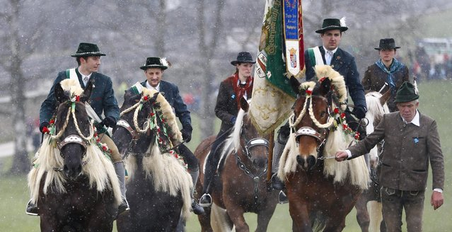 Local residents dressed in traditional  Bavarian  clothes  ride  during  the traditional Georgi (St. George)  horse riding procession on Easter Monday in Traunstein, southern Germany, Monday, April 6, 2015. (Photo by Matthias Schrader/AP Photo)