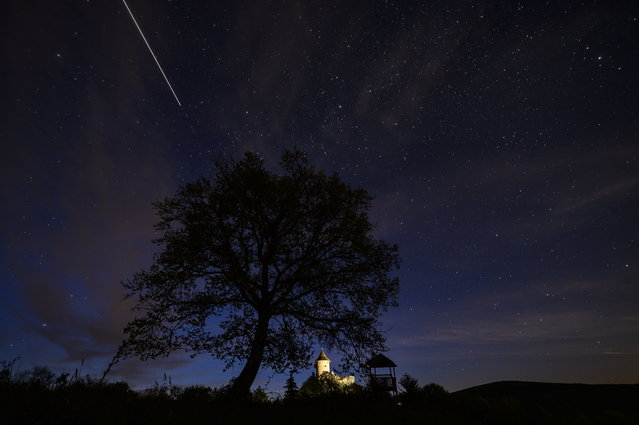Due to a long camera shutter speed the International Space Station (ISS) creates a light strip as it moves across the sky above Somosko Castle near Salgotarjan, Hungary, Wednesday, May 05, 2021. (Photo by Peter Komka/MTI via AP Photo)
