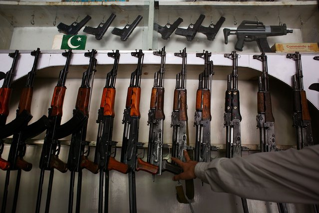 A shopkeeper shows off his wares, Russian, Chinese and Pakistani-made AK-47 assault rifles, September 10, 2006 in the tribal area of Sakhacot in western Pakistan.  The Russian AK-47 retail price was $410, the Chinese $300 and the locally made Pakistani version just $125.  (Photo by John Moore/Getty Images)