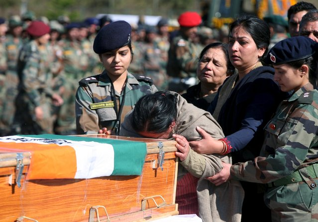 The mother of Tushar Mahajan, an Indian army officer who was killed in a gunbattle, weeps as she touches the coffin of her son Tushar during his wreath laying ceremony in Udhampur, north of Jammu, February 22, 2016. (Photo by Mukesh Gupta/Reuters)