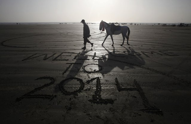 A man leads his horse as he walks past a message left by a visitor on New Year's Eve, along Karachi's Clifton Beach December 31, 2013. (Photo by Athar Hussain/Reuters)