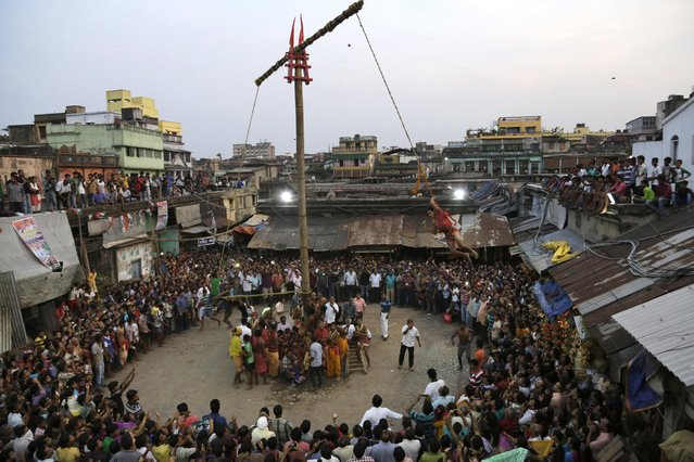 Spectators gather to watch a Hindu devotee, tied with a rope on a pole, hover around in circles during Shiva Gajan festival or Charak on the last day of Bengali calendar in Kolkata, India, Tuesday, April 14, 2015. Faithful Hindu devotees offer various such rituals each year in the hope of winning the favor of Hindu god Shiva and ensuring the fulfillment of their wishes. (Photo by Bikas Das/AP Photo)