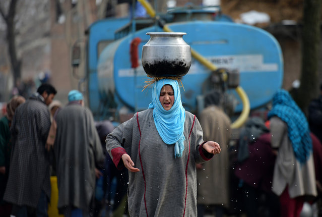 A Kashmiri woman carries a water utensil filled from a water tanker on the outskirts of Srinagar on January 19, 2017. The icy temperatures have frozen many bodies of water in Kashmir as well as drinking water taps. (Photo by Tauseef Mustafa/AFP Photo)