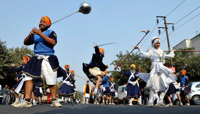 "Indian Sikh devotees show their skill in martial arts during ""Nagar Kirtan"" procession carried out as part of ""Prakash Utsav"" the birth anniversary celebrations of Guru Gobind Singh on December 29,2013 in Noida, India. Sikhs celebrated the 347th birth anniversary celebrations of Guru Govind Singh, the tenth and last guru of Sikhs. (Photo by Sunil Ghosh/Hindustan Times via Getty Images)"