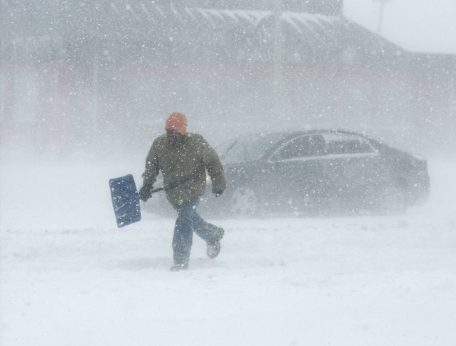 A man carrying a snow shovel walks along Market Street in Champaign, Ill., on Sunday, January 5, 2014. Icy, snow-covered roads and high winds made travel treacherous from the Dakotas and Michigan to Missouri as much of the nation braced for the next winter wallop: a dangerous cold that could break records. (Photo by Holly Hart/AP Photo/The News-Gazette)