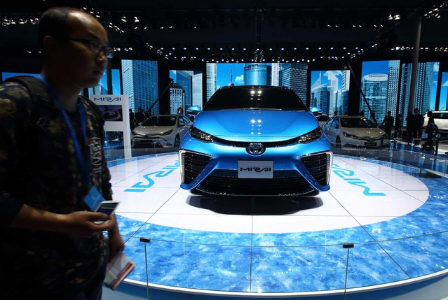 A visitor walks past a Toyota Motor Corp. Mirai fuel cell vehicle (FCV) at the 16th Shanghai International Automobile Industry Exhibition (Auto Shanghai 2015) in Shanghai, China, on Monday, April 20, 2015. (Photo by Tomohiro Ohsumi/Bloomberg)