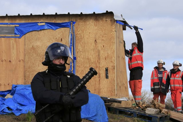 "A French riot policeman secures the area as workmen destroy a makeshift shelter during the partial dismantlement of the camp for migrants called the ""Jungle"", in Calais, northern France, February 29, 2016. Work began on Monday to clear a shanty town outside Calais used by migrants trying to reach Britain after the French government won a legal battle to dismantle part of the camp. (Photo by Pascal Rossignol/Reuters)"