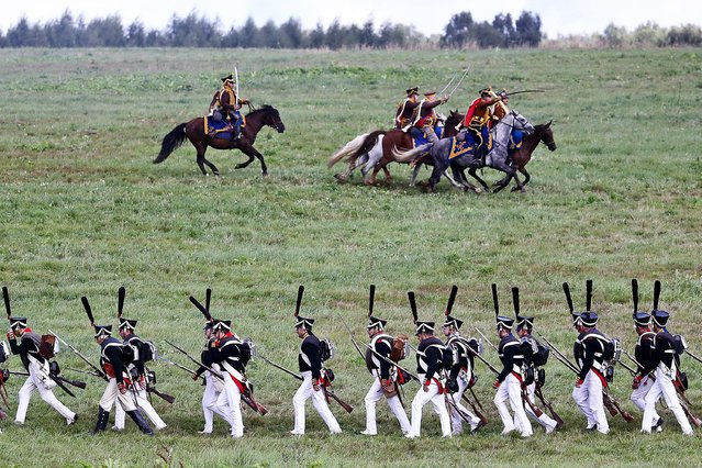 Performers wearing period uniforms take part in a reenactment of the Battle of Borodino to mark the 209th anniversary of the battle during the Day of Borodino international military historical festival in Moscow Region, Russia on September 5, 2021. (Photo by Stanislav Krasilnikov/TASS)