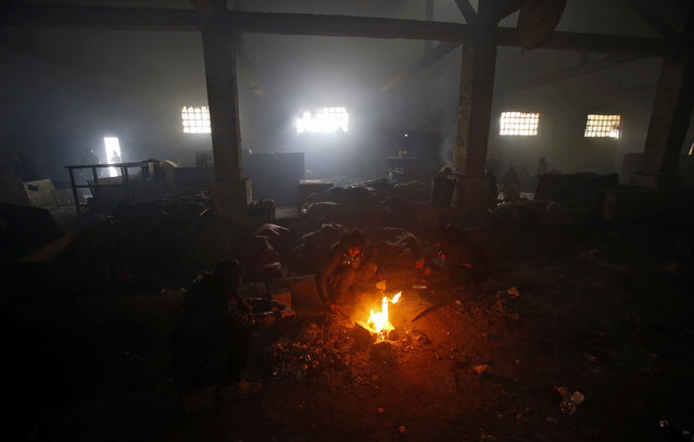 Migrants warm themselves by the fire in an abandoned warehouse in Belgrade, Serbia, Wednesday, January 25, 2017. Hundreds of migrants have been sleeping rough in freezing conditions in downtown Belgrade looking for ways to cross the heavily guarded EU borders. (Photo by Darko Vojinovic/AP Photo)