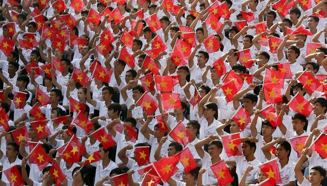Students wave the Vietnamese national flag during a rehearsal for a military parade as part of the 40th anniversary of the fall of Saigon in southern Ho Chi Minh City (formerly Saigon City), Vietnam, on April 26, 2015. (Photo by Reuters/Kham)