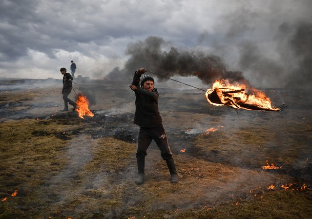 "A youth spins a flaming tire as part of a tradition marking the upcoming Clean Monday, the first day of Great Lent in the Eastern Orthodox Christian church calendar, on March 10, 2019 in the Romanian village of Poplaca. This annual ""Clean Monday"" ritual, is designed to ward off evil spirits before the onset of Lent on Monday, which marks the beginning of 40 days of abstention, when Orthodox Christians cut out meat, fish, eggs, and dairy. (Photo by Daniel Mihailescu/AFP Photo)"