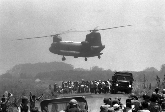 A South Vietnamese air force Chinook helicopter lifts refugees from embattled Xuan Loc area east of Saigon, April 13, 1975, as government and Communist forces continue their fight for control of the provincial capital. (Photo by AP Photo)