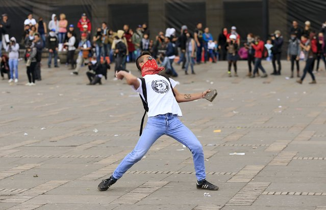 A demonstrator throws a stone during clashes against police on Labor Day in Bogota, Colombia May 1, 2015. (Photo by Jose Miguel Gomez/Reuters)