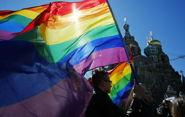 """In this Wednesday, May 1, 2013, file photo, gay rights activists carry rainbow flags as they march during a May Day rally in St. Petersburg, Russia. With the Winter Olympic Games in Sochi set to start in February, Russia has trotted out well-groomed representatives to tell the West that a law passed this summer banning homosexual """"propaganda"""" does not discriminate against gays. (Photo by Dmitry Lovetsky/AP Photo)"""