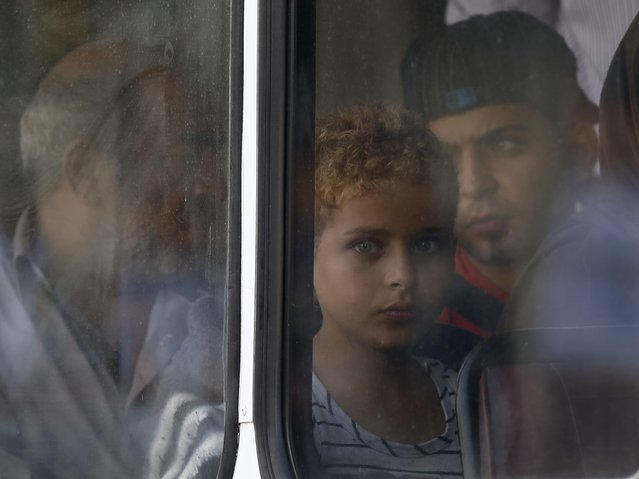 Syrian immigrant Mohamed, 12, looks out of the window of a police bus after arriving at the Armed Forces of Malta Maritime Squadron base at Haywharf in Valletta's Marsamxett Harbour in this October 12, 2013 file photo. (Photo by Darrin Zammit Lupi/Reuters)