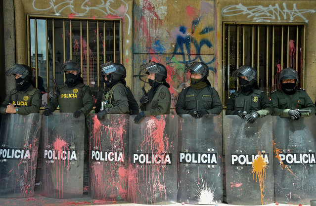 Riot police stand in a line with their shields stained with paint during a protest in Bogota, on March 17, 2016 as part of a national strike organized by labor unions to protest against the economic and social policies of President Juan Manuel Santos. (Photo by Guillermo Legaria/AFP Photo)