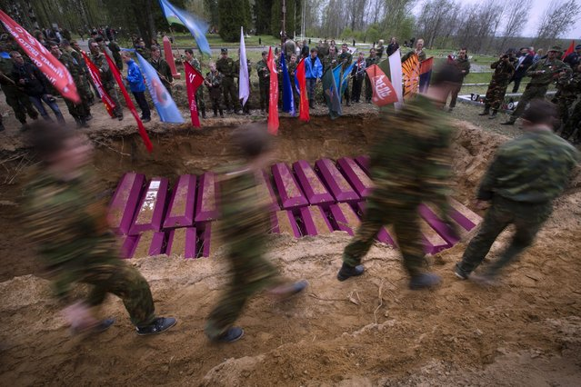 In this photo taken Thursday, May 7, 2015 photo, members of volunteer search teams walk past the grave during a reburial ceremony of remains of Soviet soldiers killed during World War II,  at the Sinyavino Heights memorial near the village of Sinyavino, 50 km (31 miles) east of  St. Petersburg, Russia. (Photo by Dmitry Lovetsky/AP Photo)