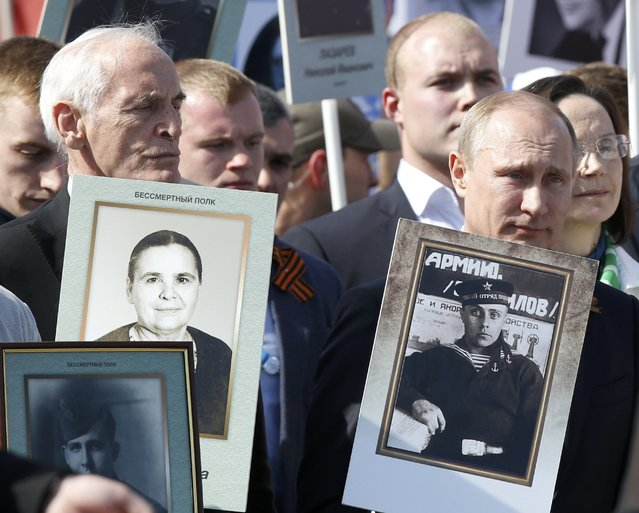 Russia's President Vladimir Putin (R, front) takes part in the Immortal Regiment march, during which people carry photos of their relatives who took part in World War Two, at Red Square in Moscow, Russia, May 9, 2015. (Photo by Sergei Karpukhin/Reuters)