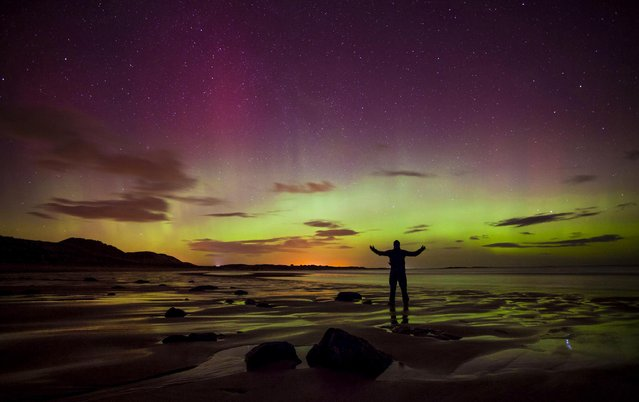 A man poses standing on a rock looking at the aurora borealis, or northern lights, illuminating the night sky at Embleton Bay in Northumberland, England, on February 27, 2014. The northern lights is a fantastical natural light display with fast moving light effects caused by particles charged by the sun colliding with particles in Earth's upper atmosphere. (Photo by Tom White/PA Wire)