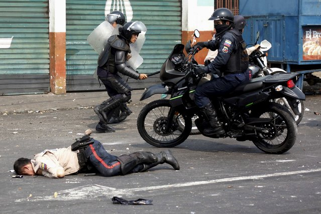 A police officer lies on the street after being run over by a bus during a protest against the increase in the price of public transport in San Cristobal, Venezuela March 29, 2016. (Photo by Carlos Eduardo Ramirez/Reuters)
