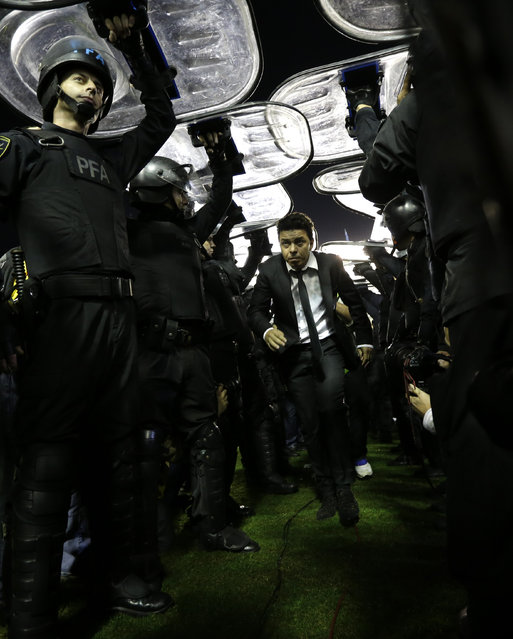 Marcelo Gallardo coach of Argentina's River Plate leaves the field under the protection of police shields after a Copa Libertadores soccer match against Boca Juniors was cancelled in Buenos Aires, Argentina, Friday, May 15, 2015. Conmebol authorities and referee Dario Herrera canceled the game after pepper spray was thrown from the stands towards River Plate players before the start of the second half of the game. (Photo by Natacha Pisarenko/AP Photo)
