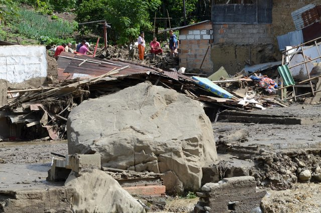 Residents stand in front of destroyed homes and streets covered in mud and debris after a landslide sent mud and water crashing onto homes in the municipality of Salgar in Antioquia department May 18, 2015. (Photo by Reuters/Stringer)