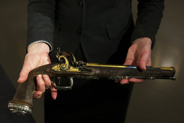 A Christie's employee handles a pistol that is part of a set made by Versailles gunsmith Nicolas-Noel Boutet and was gifted to Simon Bolivar from Marquis de La-fayette at Christie's auction house in the Manhattan borough of New York April 5, 2016. (Photo by Lucas Jackson/Reuters)
