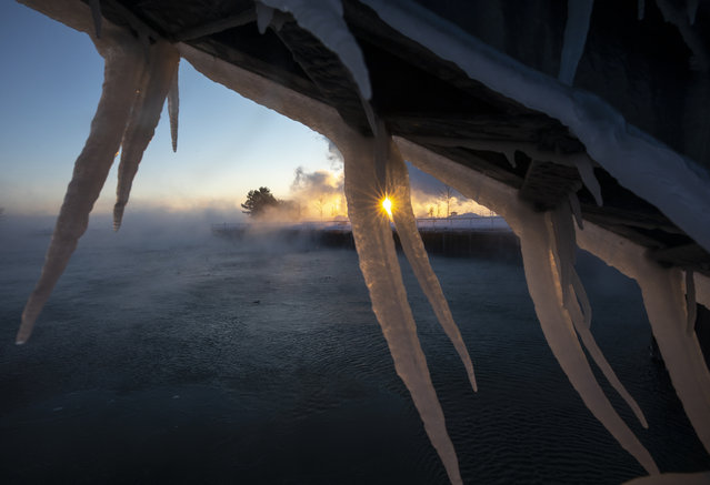 The sun rises behind icicles formed on the harbor in Port Washington, Wis., on January 30, 2019. A deadly arctic deep freeze enveloped the Midwest with record-breaking temperatures. (Photo by Jeffrey Phelps/AP Photo)
