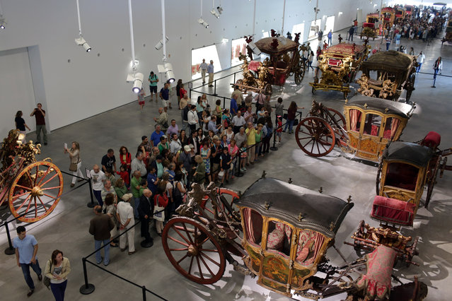 Visitors crowd the exhibition halls of the National Coach Museum in Lisbon on its 110th anniversary Saturday, May 23, 2015. The museum reopened to the public Saturday in a sleek, minimalist 21st-century building. (Photo by Armando Franca/AP Photo)