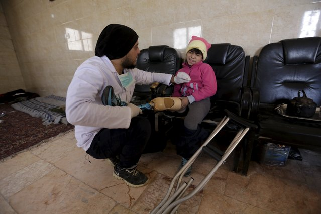 Khamis (L), 24, fits an artificial limb on nine-year-old Salma's amputated leg in the rebel-controlled area of Maaret al-Numan town in Idlib province, Syria March 20, 2016. (Photo by Khalil Ashawi/Reuters)