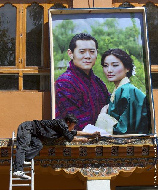 A Bhutanese worker hammers lights onto a portrait of the future King Jigme Khesar Namgyel Wangchuck, and Queen of Bhutan Ashi Jetsun Pema Wangchuck
