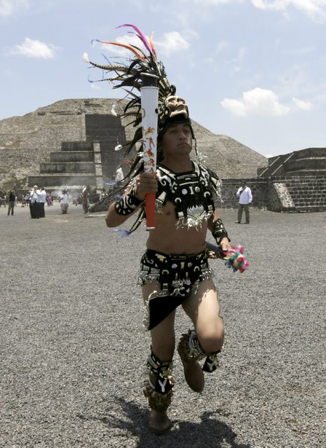 A Mexican dressed in prehispanic costumes runs with a torch of the Pan American Games during the Ceremony of the Ignition of the New Fire, at the ancient pyramids of Teotihuacan outside Mexico City May 25, 2015. (Photo by Henry Romero/Reuters)