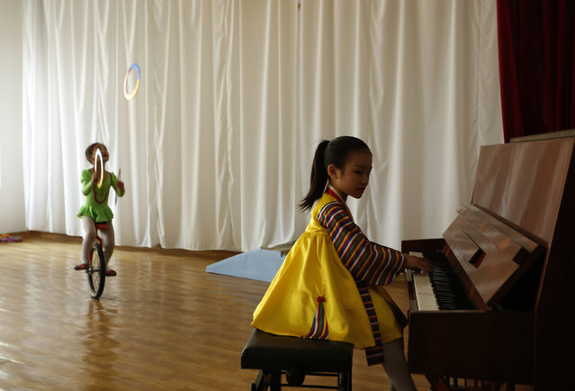 A North Korean girl plays the piano while the other on unicycles performs at the Kaeson Kindergarden in Pyongyang, North Korea Tuesday, April 24, 2012. (Photo by Vincent Yu/AP Photo)