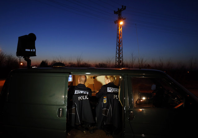 FILE - In this Feb 13, 2015 file photo members of the German border police sit in a van as they check a security camera while monitoring a stretch of the Serbian border with Hungary in the village of Hajdukovo, some 180 kilometers north of Belgrade, Serbia. Hungary's foreign minister said Wednesday, June 17, 2015 the government is considering building a 4-meter-high (13-foot-high) fence along border with Serbia to stop the flow of migrants reaching the country. (AP Photo/Darko Vojinovic)