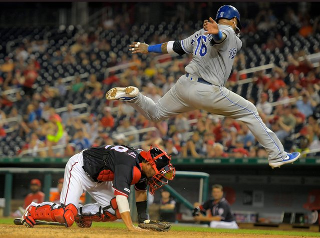 Kansas City Royals' Martin Maldonado, right, vaults over Nationals catcher Kurt Suzuki after scoring a run in the 11th inning during their baseball game at Nationals Park in Washington, D.C. on July 5, 2019. (Photo by John McDonnell/The Washington Post)