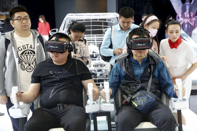 Visitors use VR experience technology at the booth of Kia Motors during the Auto China 2016 auto show in Beijing April 26, 2016. (Photo by Kim Kyung-Hoon/Reuters)