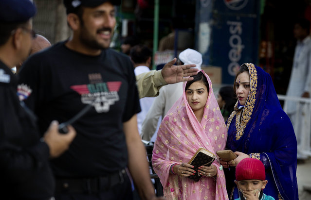 In this Thursday, April 14, 2016 photo, Pakistani Sikh women wait at a police barrier to attend a religious festival known as Beshakhi in Hasan Abdal, Pakistan. Earlier this month, the gurdwara in Peshawar's crowded Old City opened its doors to worshippers for the first time in 73 years. The reopening was celebrated by Pakistan's tiny Sikh minority, but security is a constant concern. (Photo by B.K. Bangash/AP Photo)