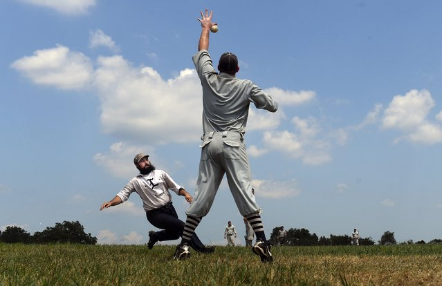 """Lawrence Major, 29, of Somerville, N.J., from the Liberty Base Ball Club of New Brunswick slides safely into home as Steve """"Lefty"""" Scharff, 37, of Williamstown, N.J., from the Lewes Base Ball Club fields the ball during the National 19th Century Base Ball Festival in Gettysburg, Pa. on July 21, 2019. (Photo by Matt McClain/The Washington Post)"""